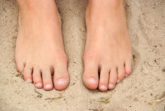Two feet in the sand Stock Photo