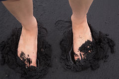 Two feet sinking into the black sand Stock Photography
