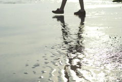 Two feet walking and reflecting on a beach. The feet of someone walking on a beach at low tide. Their feet and legs are reflected in the wet sand stock photo