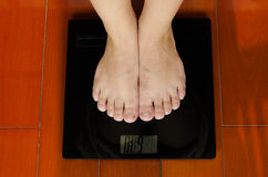 Two feet on the weighing-machine stock image