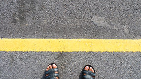 Two feet were crossing the yellow line traffic. On asphalt road Stock Photography