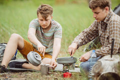 Two fellow campers making tea and preparing food Royalty Free Stock Images