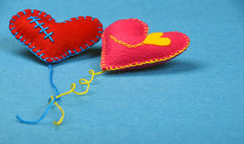 Two felt craft art hearts, pink and red on blue Royalty Free Stock Photo