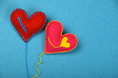 Two felt craft art hearts, pink and red on blue Stock Photos