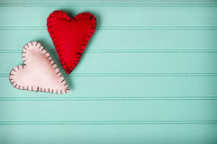 Two felt hearts. On a retro turquoise background Stock Photos