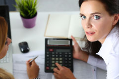 Two female accountants counting on calculator Stock Photos