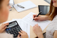 Two female accountants counting on calculator income for tax form completion hands closeup. Internal Revenue Service. Inspector checking financial document Royalty Free Stock Photos