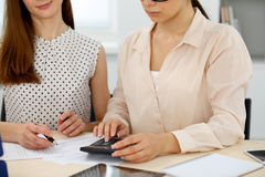 Two female accountants counting on calculator income for tax form completion hands closeup. Internal Revenue Service Royalty Free Stock Photos
