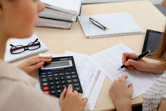 Two female accountants counting on calculator income for tax form completion hands closeup. Internal Revenue Service Stock Images