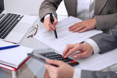 Two female accountants counting on calculator income for tax form completion hands closeup. Internal Revenue Service. Inspector checking financial document Stock Image