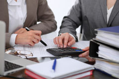 Two female accountants counting on calculator income for tax form completion hands closeup. Internal Revenue Service. Inspector checking financial document Royalty Free Stock Image