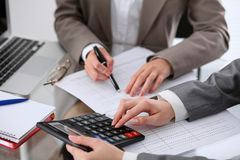 Two female accountants counting on calculator income for tax form completion hands closeup. Internal Revenue Service royalty free stock photography