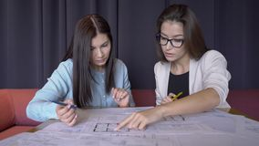 Two female achitects work on the city bevelopment plan in their office. Businesswomen prepares for the presentation of their project. The ladies sit on the stock video