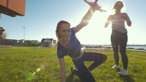Two female acrobat having fun on the grass during workout under the sun. Slow motion stock video footage