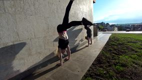 Two female acrobat performs handstand on the wall at sunset outdoors. Close up stock video footage