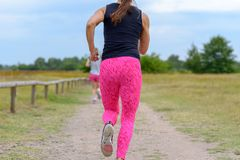 Two female adult jogger running away from camera. Along unpaved road with wooden fence at one side and field on the other stock images