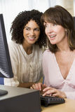 Two female adult students working on a computer Stock Image