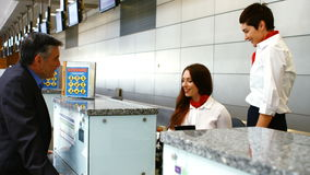 Two female airport staff checking passport and interacting with man at check-in desk. Two female airport staff checking passport and interacting with man at stock video footage