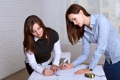 Two female architects studying blueprints areas Royalty Free Stock Photo