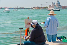 Two female artists painting in Venice. VENICE - APRIL 27, 2012: Two unidentified artists paint the Canal Grande with Basilica Santa Maria della Salute in the royalty free stock photography