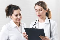 Two female assistants dressed in white coats talking to each other in the dentistry center. White and blured background. Healthcare idea royalty free stock images
