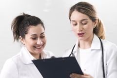 Two female assistants dressed in white coats talking to each other in the dentistry center. White and blured background. Healthcare idea stock images