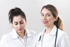 Two female assistants dressed in white coats talking to each other in the dentistry center. White and blured background. Healthcare idea. Smiling blonde girl royalty free stock photos