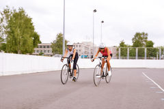 Two female athletes competing in bike race outdoors. Royalty Free Stock Image