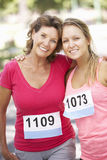 Two Female Athletes Competing In Charity Marathon Race Stock Photo