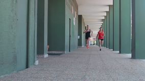 Two female athletes running. Through the arcades of a building stock video