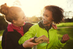 Two female athletes smiling and hugging after workout in park Royalty Free Stock Photo