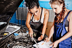 Two female auto mechanic repairing a car Stock Photos