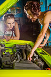 Two female auto mechanic repairing a car Royalty Free Stock Photography