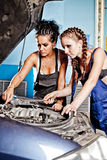 Two female auto mechanic repairing a car. Working on the transmission Stock Photos