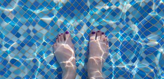 Female bare feet seen through blue waters of a swimming pool royalty free stock images