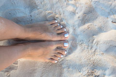 Two female bare feet on white sand Stock Image