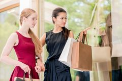 Two female best friends looking at the latest fashion trends stock photography