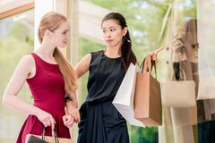Two female best friends looking at the latest fashion trends whi Royalty Free Stock Photography