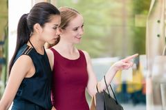 Two female best friends looking at the latest fashion trends whi royalty free stock photo