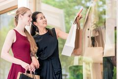 Two female best friends looking at the latest fashion trends whi Royalty Free Stock Images