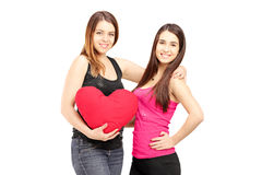 Two female best friends standing close together and holding a re Royalty Free Stock Images