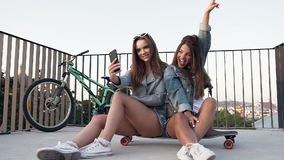 Two female best friends taking selfie with smartphone when sitting on skateboarding while walking at summer sunny day