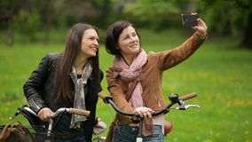 Two Female Bicyclists in Jackets and Scarves are Taking Photo by Smartphone. Young Beautiful Brunettes with Bicycles are stock footage