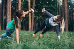 Two female buddies doing partner side plank giving high five while training in the forest royalty free stock photography