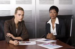Two female business (blond). Multi-racial business team working within an office with a sales graphs Royalty Free Stock Image