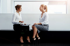 Two female business partners having pleasant conversation after working on touch pad while sitting in office interior, Royalty Free Stock Image