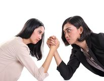 Two female business workers face each other in arm wrestling battle, white background stock photos