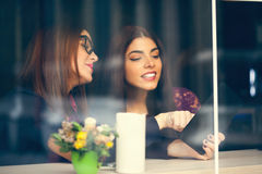 Two Female In Cafe Using Technology Stock Photo