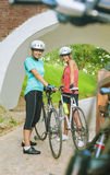 Two Female Caucasian Cyclists Standing Outdoors Smiling Stock Photography