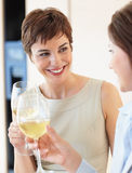 Two female celebrating with a glass of white wine Royalty Free Stock Images